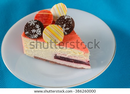 Floating Raspberry White Chocolate Mousse with chocolate coin topping on blue fabric background - stock photo
