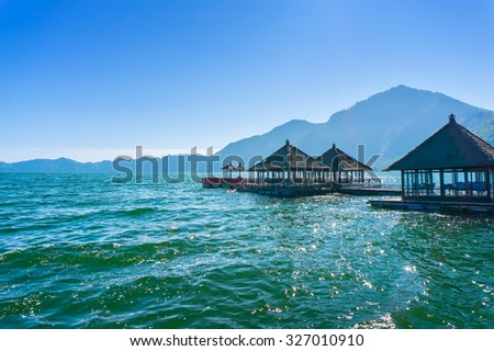 floating restaurant at batur lake with blue sky background, bali indonesia - stock photo