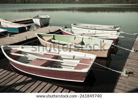 Floating Wooden Boats with Paddles and Its Reflection in a Water. Filtered shot - stock photo