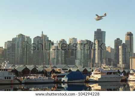 Floatplane Over Coal Harbor, Vancouver. A commuter floatplane comes in for a landing in Vancouver's Coal Harbor. British Columbia, Canada. - stock photo