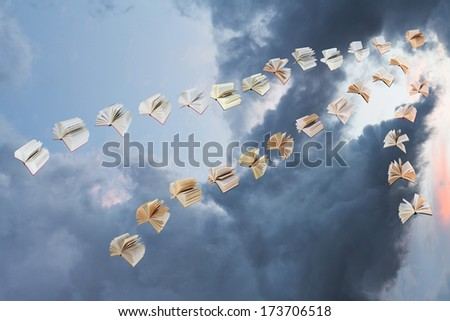 flock of flying books with storm clouds background