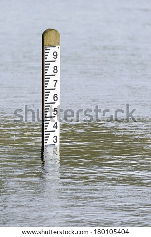 Flood level depth marker post with rain falling into the surrounding water - stock photo
