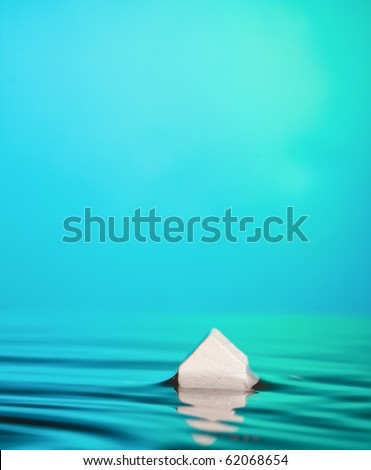 Flood or foreclosure Concept. Abstract Macro of a little white house in blue-green water with ample copy-space. - stock photo