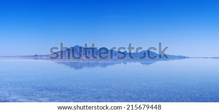 flooded Bonneville Salt Flats with distant mountains and blue sky reflection - stock photo