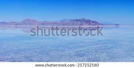 flooded Bonneville Salt Flats with reflection of distant peaks and blue sky - stock photo