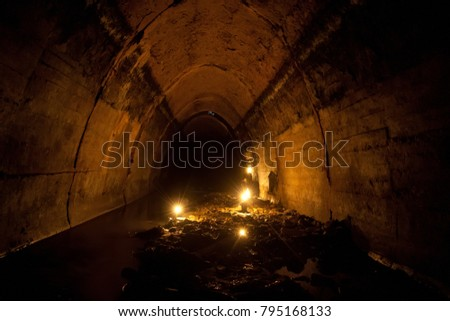 Flooded by dirty industrial wastewater sewage collector. Sewer tunnel under city Voronezh full of garbage  illuminated by candles