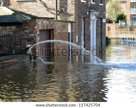 Flooded city street leading to swollen River Ouse. York, North Yorkshire, UK. - stock photo