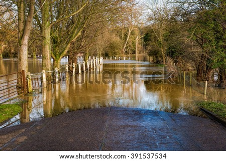 Flooded English country road by the river in the month of March - stock photo