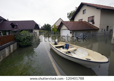 Flooded house after heavy rain with motor boat on the street. - stock photo