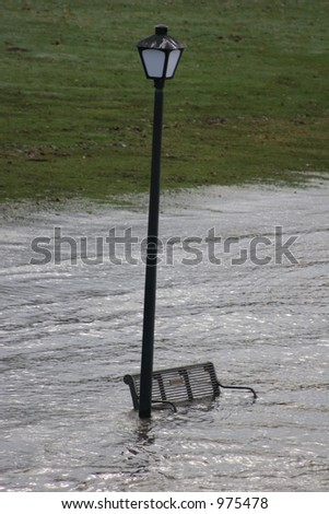 Flooded lamp and bench - stock photo