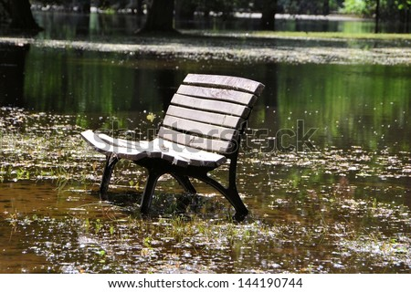 flooded park with a bench while flooding in Magdeburg - stock photo