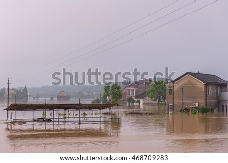 flooded road junction with House in floodwater on rainy day.