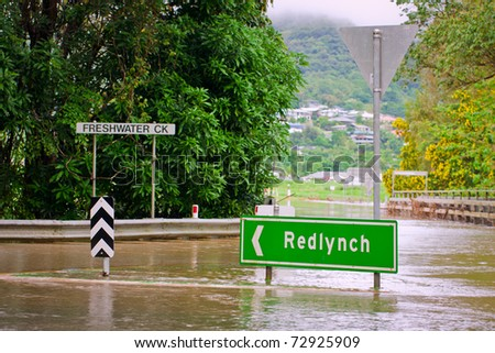 Flooded roundabout, road signs and bridge in Queensland, Australia after heavy rain - stock photo