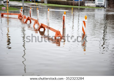 Flooded transportation sign with road barriers on a cloudy day. - stock photo