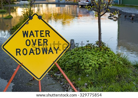 Flooding Disaster Water Over Roadway Street Sign Reflective Pond - stock photo