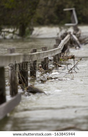 Flooding river over the wooden fence. - stock photo