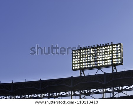 Floodlights over baseball stadium at dusk, with copy space - stock photo