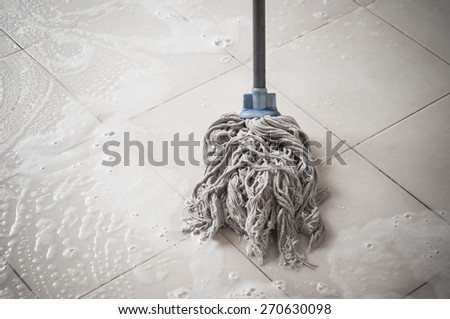 Floor cleaning with mob and cleanser foam. - stock photo
