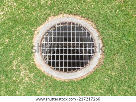 Floor drain contrast with green grass background in the garden - stock photo