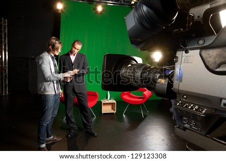 Floor manager and presenter planning a television broadcast with a studio camera in the foreground - stock photo