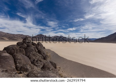 Floor of a dry Racetrack Playa lake with cracked mud, blue sky, clouds and mountains. Racetrack Playa. Death Valley national park. California. USA. - stock photo