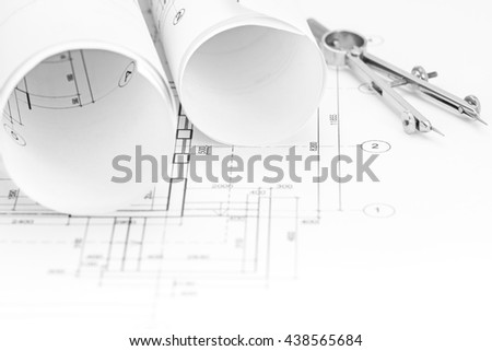 floor plan background with blueprints rolls and drawing compass - stock photo