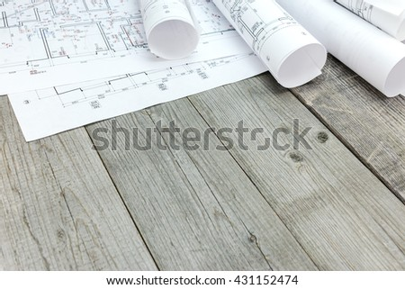 floor plan drawings with architectural blueprint rolls on wooden desk - stock photo