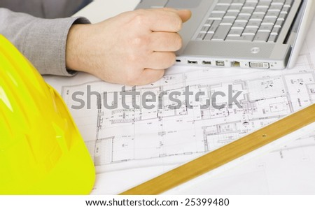 Floor plan on architect's desk along with laptop computer, yellow hardhat and ruler.