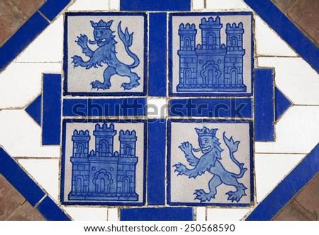 Floor tile with heraldic symbols of Leon and Castile, Spain - stock photo