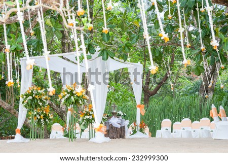 Floral arrangement at a wedding ceremony on the beach. - stock photo