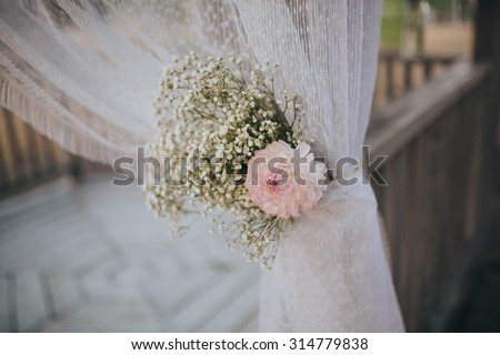 floral arrangement of flowers and greenery decorate the arch for the wedding ceremony - stock photo