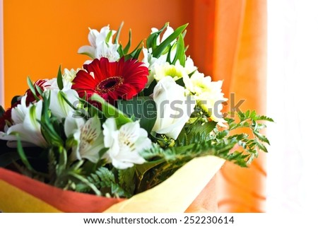 Floral celebrating bouquet of different flowers on blurred multicolored background. Selective focus - stock photo