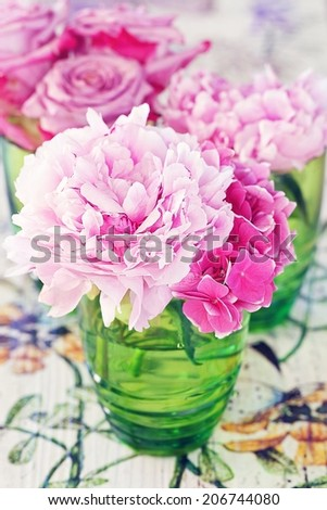Floral composition with a peony and roses in a glass vase. Pink flowers on a colorful table . - stock photo