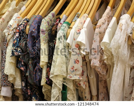 Floral design summer dresses on hangers on store rack - stock photo