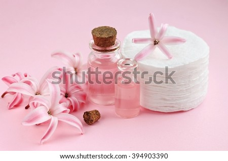 Floral facial tonic in bottles, hyacinth flower scent, cotton pads. Pink background. - stock photo