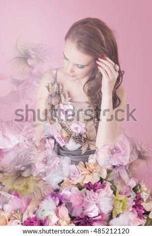 Floral fantasy woman wearing a dress of flowers posing in front of a pink background