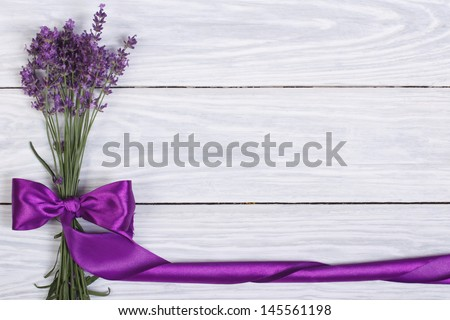 floral frame from flowers of lavender and purple ribbon on a wooden surface - stock photo