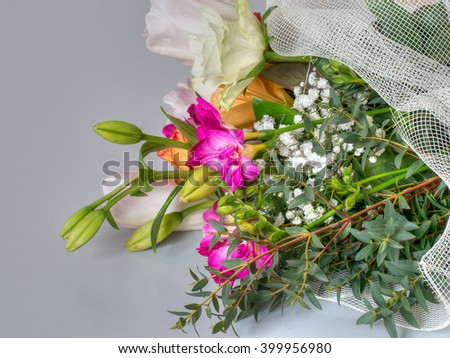 Floral gift. Bouquet lying on soft grey background. Looks rather sad. Memorial, funeral flowers maybe.  - stock photo