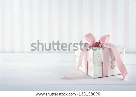 Floral pattern gift box tied with pink ribbon on white wooden background with copy space - stock photo