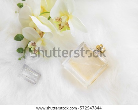 Floral perfume bottle with yellow orchid, overhead shot