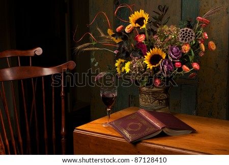 Floral still life with wine and gold embossed leather bound book, on an antique wooden table. Low key, dark background, spot lighting, and rich Old Masters colors. Horizontal format  and copy space. - stock photo