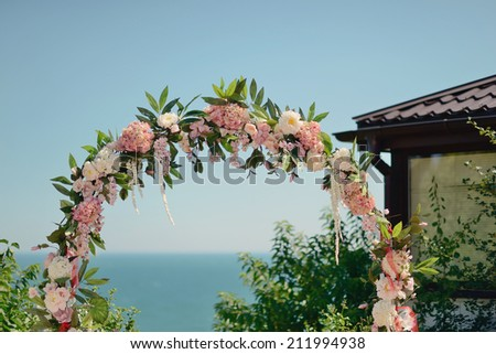 floral wedding arch against the blue sky and sea - stock photo