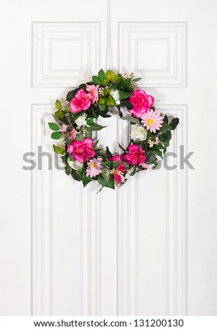 Floral wreath hanging on white wood door - stock photo