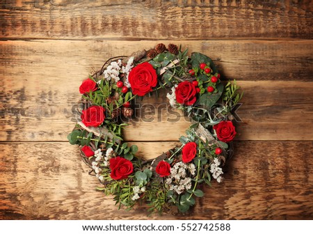 Floral wreath with beautiful flowers on wooden background