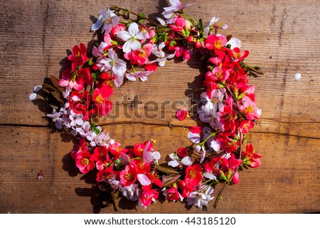 Floral wreath with beautiful spring flowers on wooden background