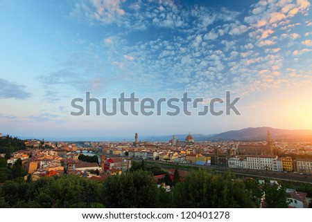 Florence city with green trees on the foreground with fluffy clouds in a sky at sunrise