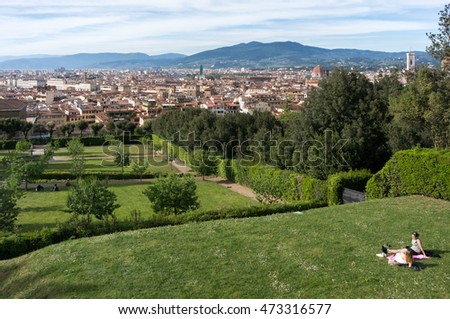 Florence, Italy - April 20, 2016. People relaxing on the lush lawns of Boboli gardens with great view of Florence, landscape of red roofs and tuscany hills on a horizon, Italy