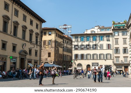 FLORENCE ITALY - APRIL 21; Piazza Del Duomo as would have been, people crowd  street with typically Italian urban architecture and iconic retro Martini neon sign on April 21, 2011 in Florence Italy. - stock photo