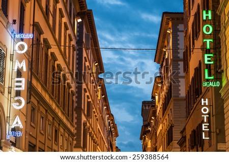 FLORENCE, ITALY - JANUARY 17: Hotel Bigallo and Omega neon signs at Via dei Calzaiuoli on January 17, 2015 in Florence, Italy. Florence receives about 7 million visitors each year. - stock photo