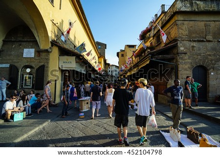 Florence, Italy - JUL. 1st, 2016: Street View of Ponte Vecchio, a medieval stone bridge over the Arno River in Florence. It is famous for still having shops built alog the bridge. - stock photo